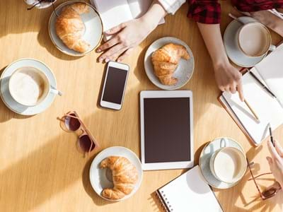 overhead view of young women sitting at coffee break with digital devices, business lunch - stock photo