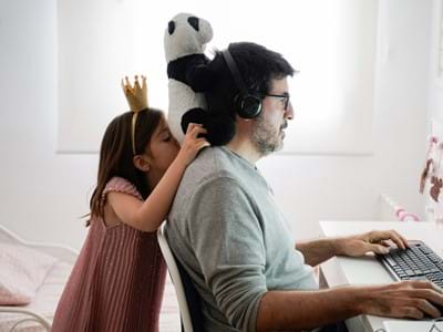 man working on computer with daughter