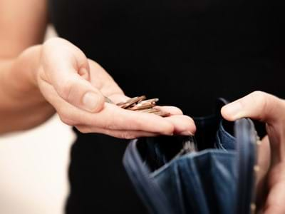 Woman counting money in purse benefits